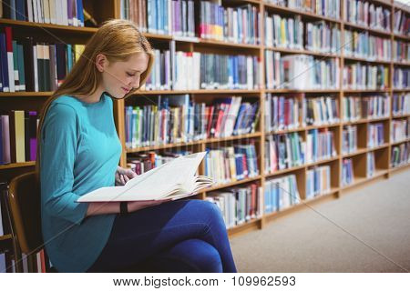 Smiling student sitting on chair reading book in library at the university