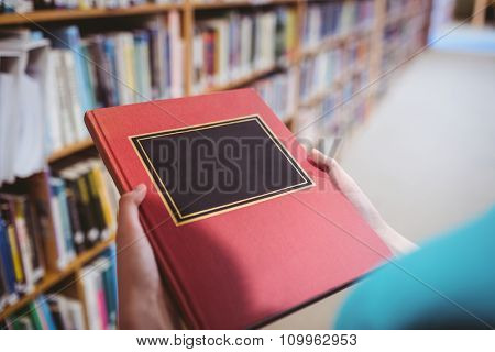 Over shoulder view of student in library holding book at the university