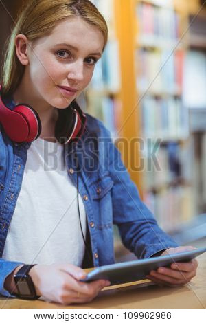 Pretty student with headphones using tablet in library at the university