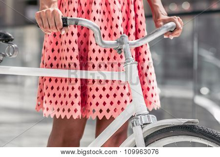 woman in pink dress with bicycle