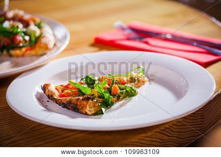 Delicious appetizer on white plate with fork and knife on red napkin close up
