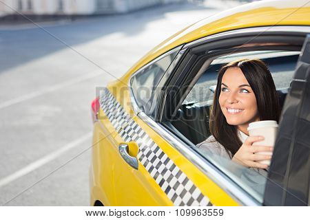Young girl with coffee in a taxi