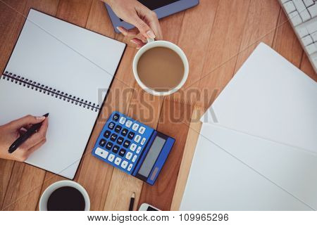 Cropped image of woman writing on notepad in her office