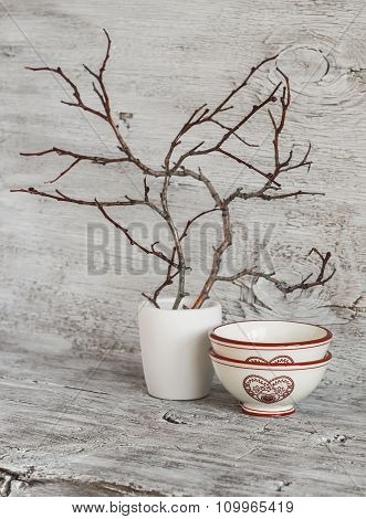 Dried Branch In White Gypsum Vase And Ceramic Bowl On A White Rustic Wooden Table. Vintage And Rusti