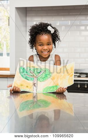 Smiling girl showing his drawing in the kitchen