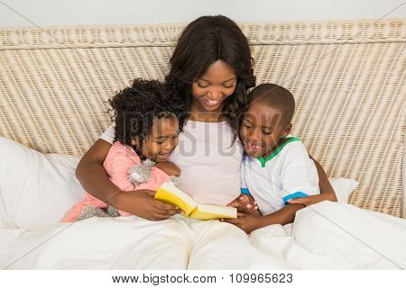 Mother and children reading book together in bed