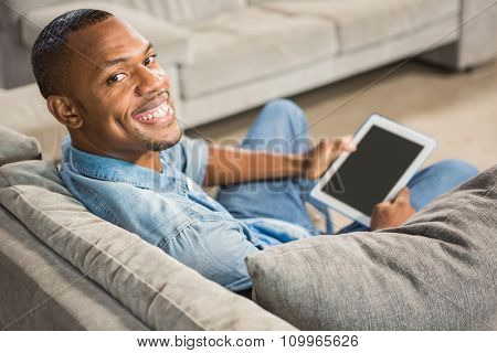 Over shoulder view of casual man using tablet in living room