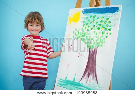 Happy boy with thumbs up beside easel