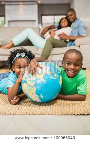 Happy siblings lying on the floor holding globe in the living room