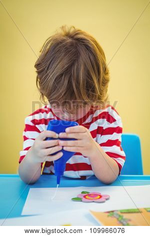 Small boy using a bottle of glue at the desk