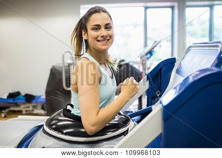 Smiling woman using an anti gravity treadmill at the gym