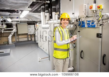 Engineer checking the temperature pipes in the control room
