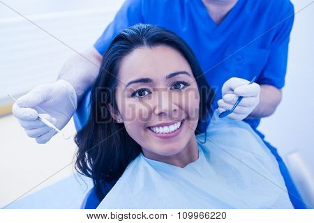 Dentist examining female patient teeth in dental clinic