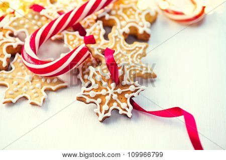 Christmas Gingerbread Homemade Cookies and Candy Canes over wooden table background. Traditional Holiday Sweets