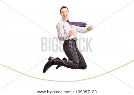 Delighted businessman jumping over a rope and gesturing joy isolated on white background