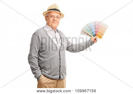 Studio shot of a senior gentleman holding a color swatch and looking at the camera isolated on white background