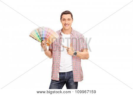 Cheerful young man holding a color swatch in one hand and pointing towards it with the other isolated on white background