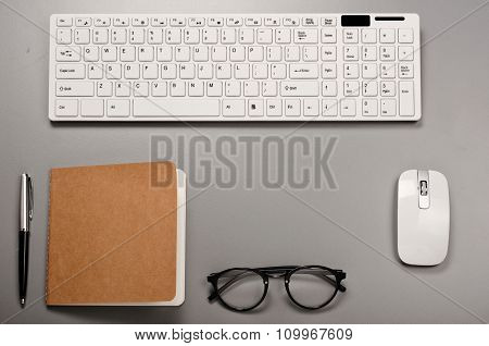 Office Workstation With A Keyboard, Notebook, Pen And Glasses