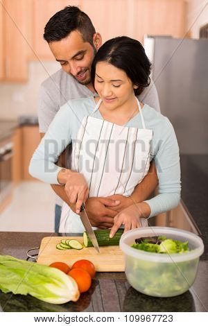 lovely young indian couple chopping vegetables together in the kitchen