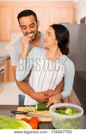 romantic indian woman feeding boyfriend slice of cucumber