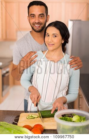 beautiful indian couple cooking together in home kitchen