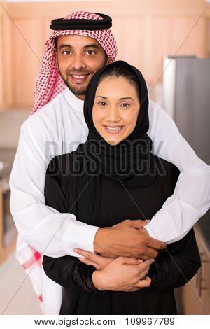 portrait of happy muslim man hugging his wife