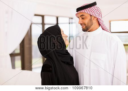 happy arabian couple looking at each other at home