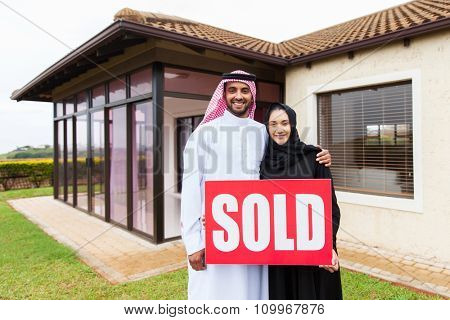 happy arabian couple  in front of new home with sold real estate sign