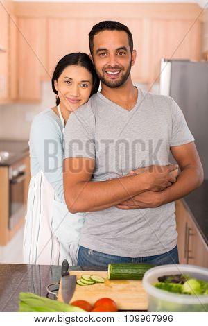 romantic indian couple embracing in kitchen while preparing dinner