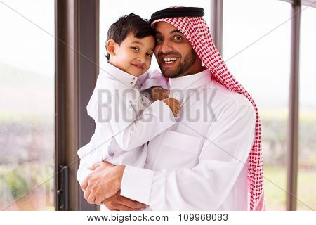 happy muslim father and son indoors