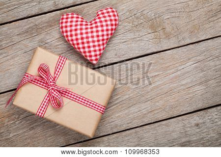Valentines day toy heart and gift box over wooden table background