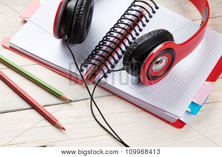 Office wooden desk with notepad and headphones