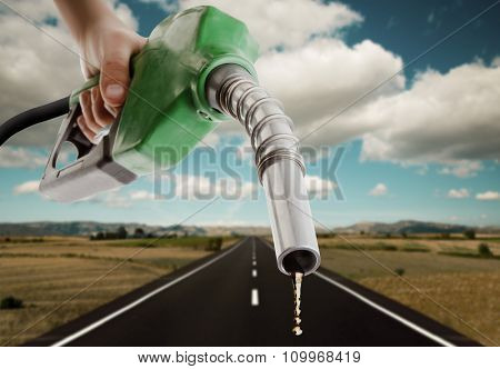 Male hand holding gas pump with one last drop and the road on the background