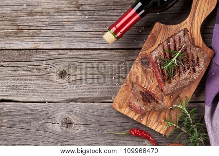 Grilled beef steak with rosemary, salt and pepper and wine bottle on wooden table. Top view with copy space