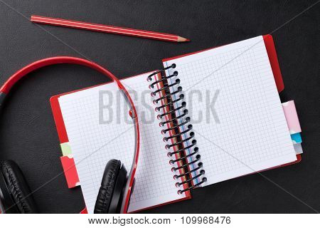 Office leather desk with notepad and headphones. Top view with copy space