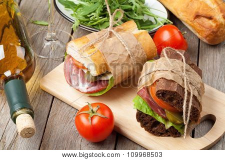 Two sandwiches and white wine on wooden table