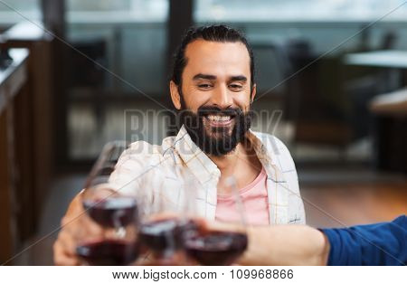 leisure, eating, food and drinks, people and holidays concept - happy man with friends clinking glasses of wine at restaurant