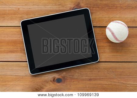 sport, technology, game and objects concept - close up of baseball ball and tablet pc computer on wooden floor