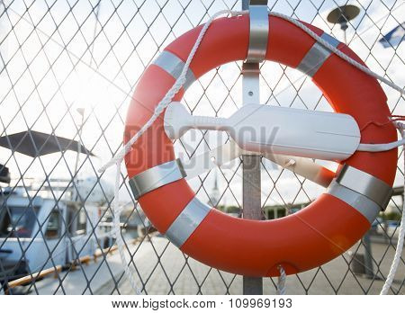 sailing, safety and life rescuing concept - lifebuoy hanging on fence over moored boats on pier