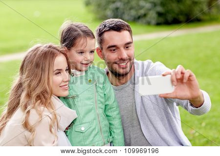 family, childhood, technology and people concept - happy father, mother and little daughter taking selfie by smartphone in park