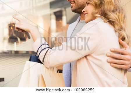 sale, consumerism and people concept - close up of happy couple with shopping bags looking at shop window in city