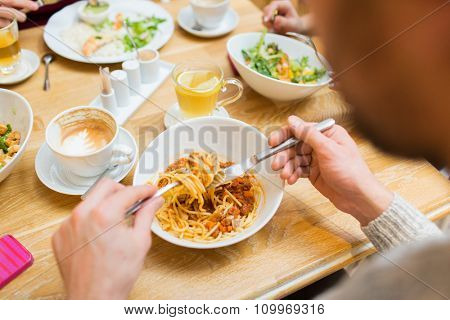 people, leisure and food concept - close up man eating pasta for dinner at restaurant or home