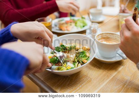 people, leisure and food concept - close up friends having dinner and eating at restaurant
