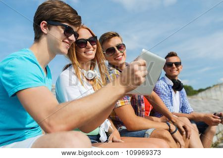 friendship, leisure, summer, technology and people concept - group of smiling friends with tablet pc computer sitting outdoors