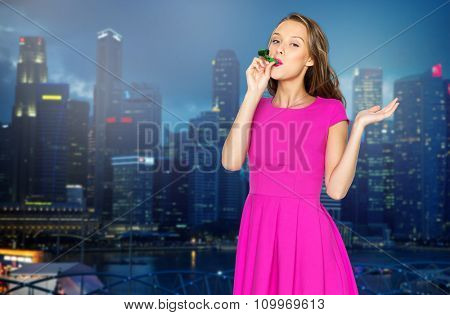 people, holidays and celebration concept - happy young woman or teen girl in pink dress blowing to party horn over night singapore city background