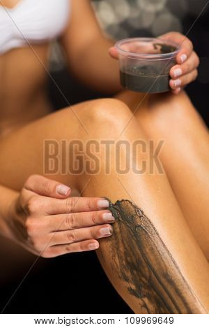 people, beauty, spa, healthy lifestyle and relaxation concept - close up of woman applying therapeutic mud to her body in bath