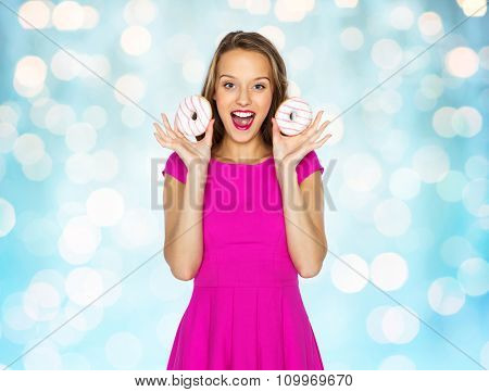 people, holidays, junk food and fast food concept - happy young woman or teen girl in pink dress with donuts over blue holidays lights background