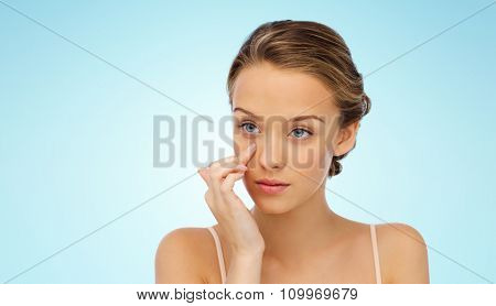 beauty, people, cosmetics, skincare and health concept - young woman applying cream to her face over blue background