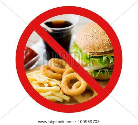 fast food, low carb diet, fattening and unhealthy eating concept - close up of hamburger or cheeseburger, deep-fried squid rings and french fries behind no symbol or circle-backslash prohibition sign