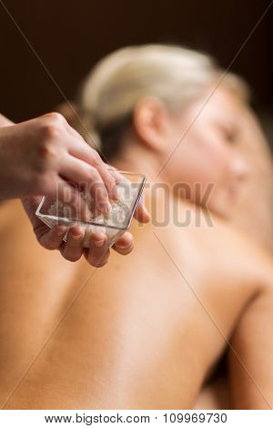 people, beauty, massage and relaxation concept - close up of young woman lying and therapist holding salt bowl in spa